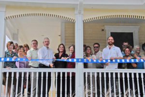 CFC employees hold blue ribbon at the Chamber of Commerce ribbon cutting event.