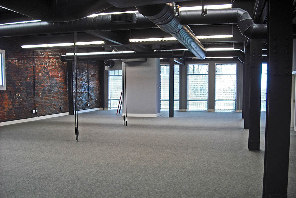 Renovated Wick's Building 3rd Floor shows an open floor plan with an exposed brick wall, black ventilation system on the ceiling, and a wall of windows along the back.