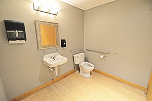 Faris, Suite 110, has a spacious restroom with a soap and paper towel dispenser.