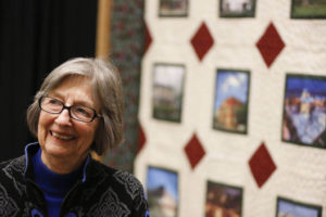 Gayle Cook, co-founder of Cook Medical, stands in front of CFC 30th anniversary quilt at the Indiana Heritage Quilt Show.